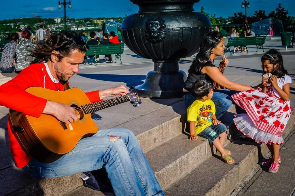 Guitarist on the steps at Quebec City boardwalk.