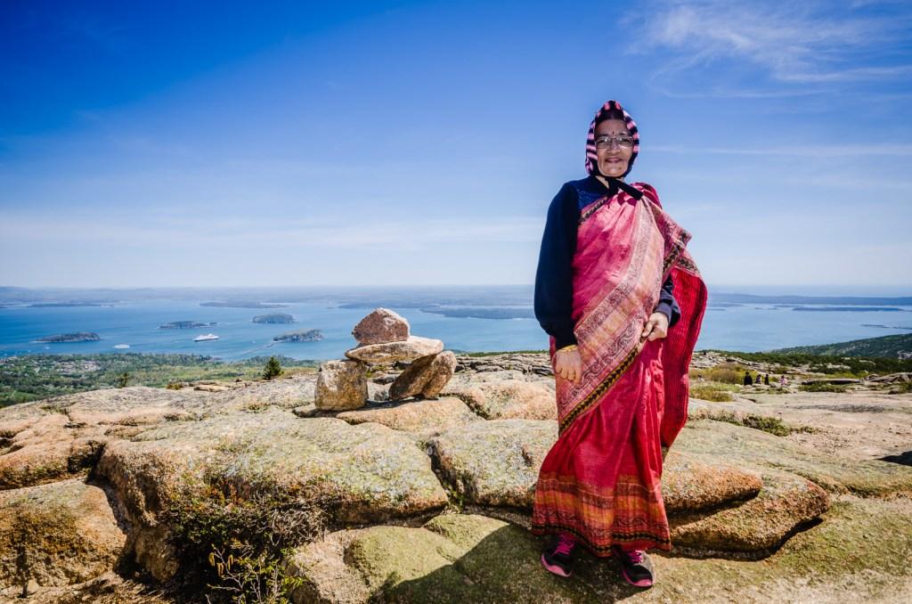 Indian matron wearing a pink sari stand next to a cairn atop Cadillac Mountain in Acadia National Park.