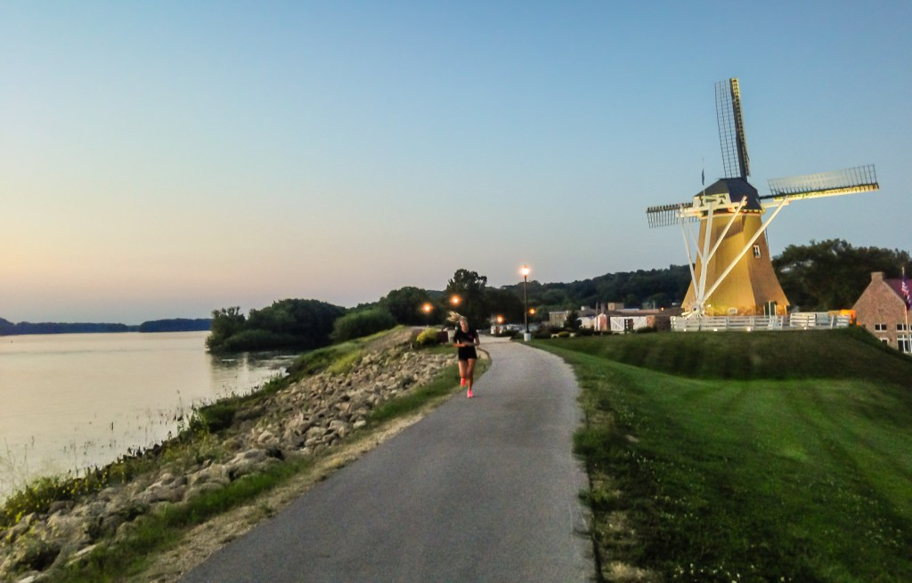 Woman running past Dutch Windmill on the Great River Trail along the Mississippi River.