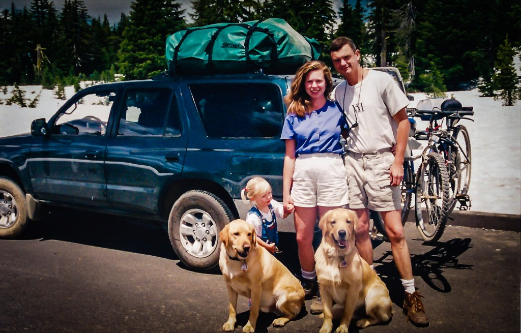 David and Sandra Foyt posing with toddler Kayla and their two retrievers, Mowgli and Spock, in front of their fully loaded Toyata 4Runner.