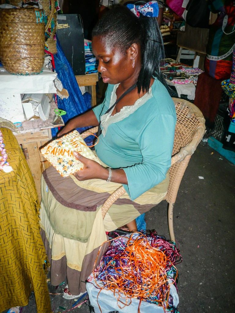 Woman embroidering straw bag at The Straw Market in Nassau Bahamas.