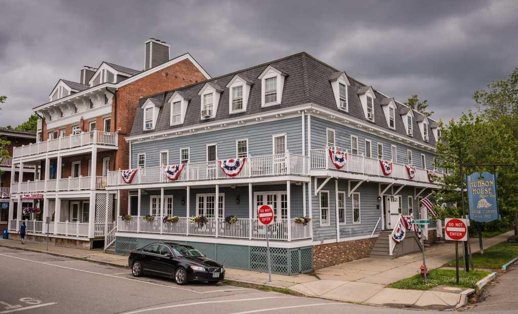 Flag festooned exterior of historic hotel Hudson House Inn in Cold Spring, New York.