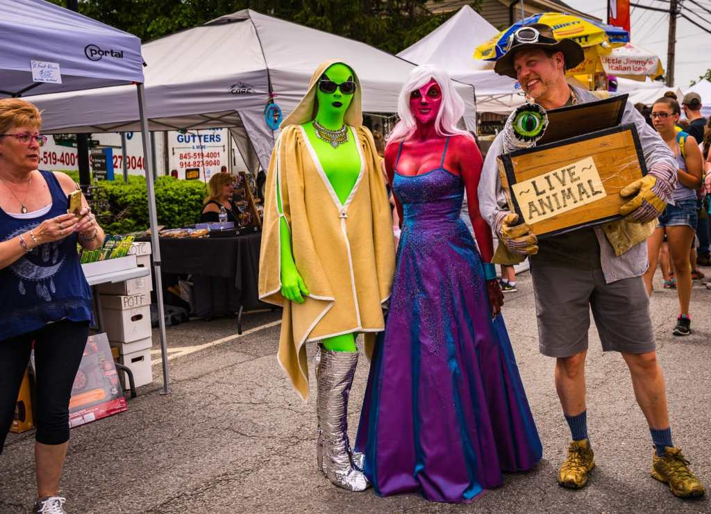 A man dressed in a safari hunter costume carries a box labelled Live Animal that has a one-eyed extraterrestrial popping out. Next to him, two women dressed as aliens pose with him as a tourist captures the image on an iPhone.