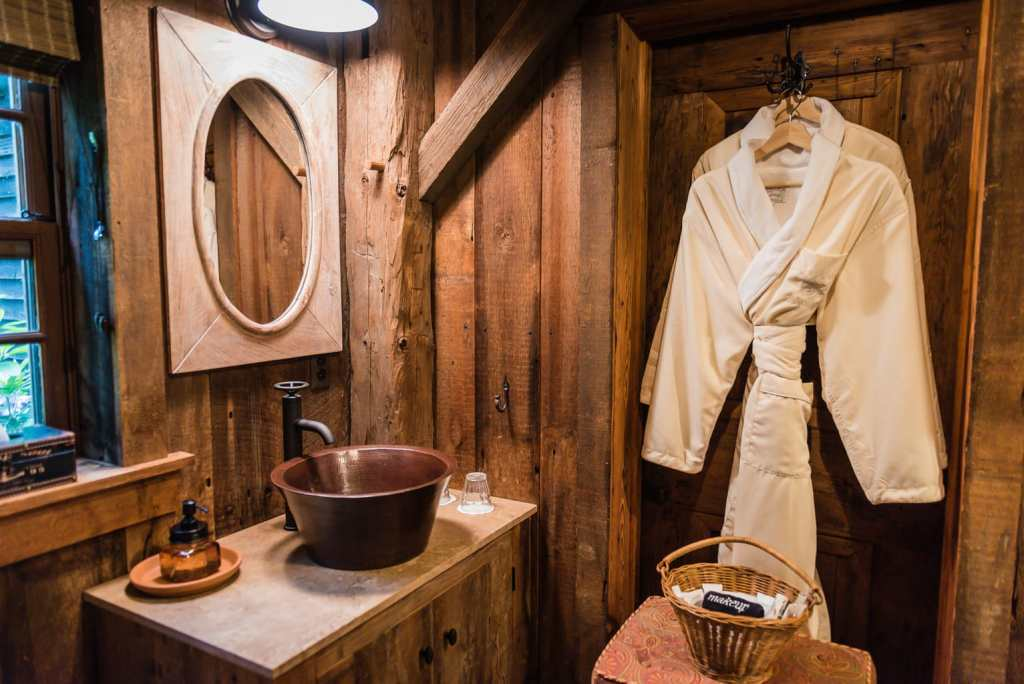 Bathrobes and amenities in rustic bathroom with copper sink at Hudson Valley Rose Bed and Breakfast in Middletown NY.