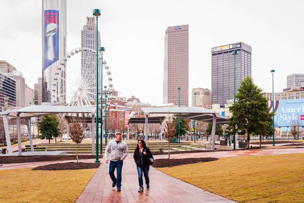 Couple walks in Centennial Olympic Park with Atlanta GA skyline in background.