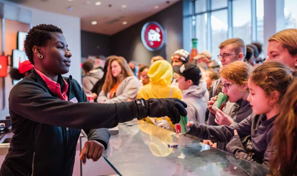 Employee hands out free cans of soda at beginning of World of Coca Cola tour in Atlanta GA.