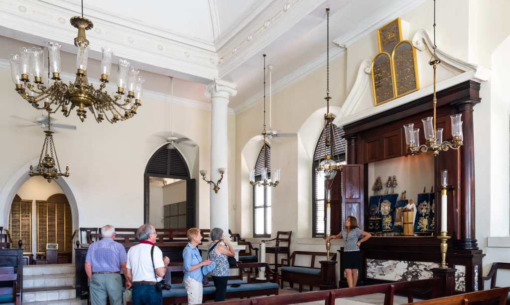 Interior of St. Thomas Synagogue with tourists and sand floor in St. Thomas US Virgin Islands