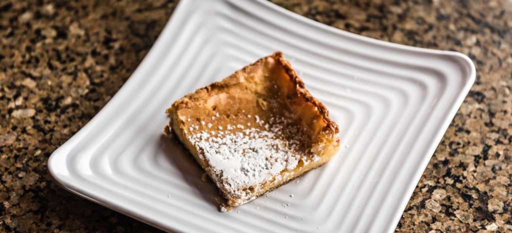 Square of Gooey Butter Cake with powdered sugar sprinkled on top served on white plate at Parker Coffee in St. Louis MO.