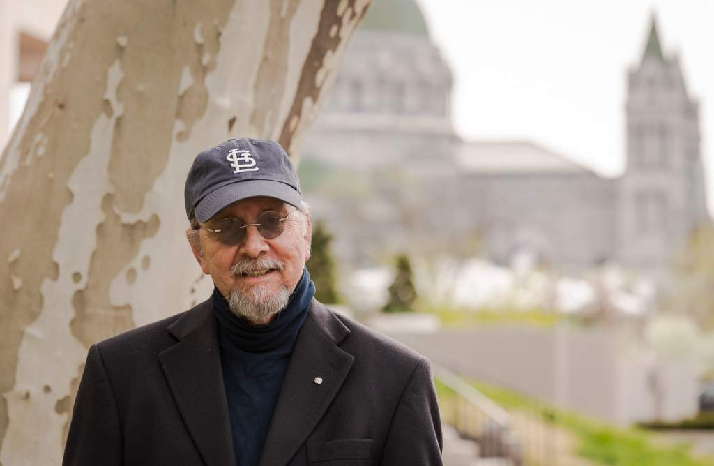 Man wearing St Louis Cardinals baseball cap with Cathedral Basilica in the background.