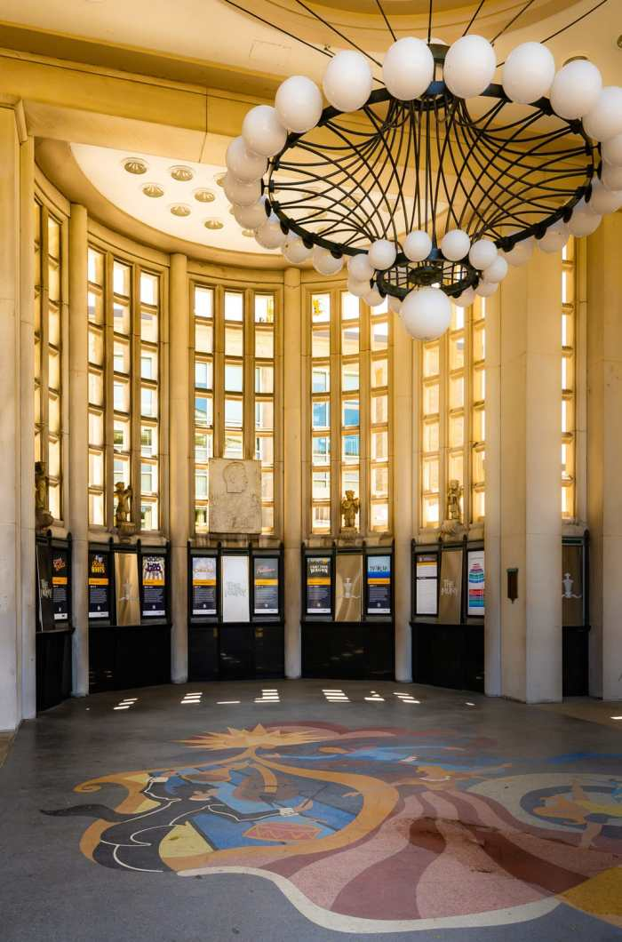 Box office posters under grand interior rotunda at The MUNY.