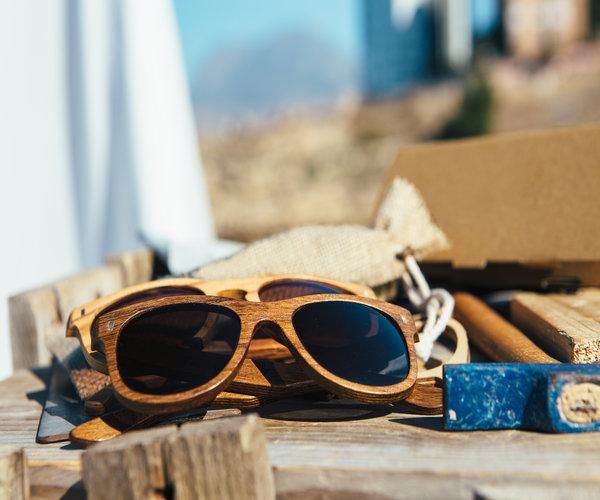 Close up shot van houten zonnebrillen op een houten tafel. De zonnebrillen zijn zojuist gemaakt. Er ligt een hamer bij.