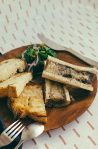 Shot of bone marrow, toast and salad on a wood plate against a sheet of fabric - The Mummy