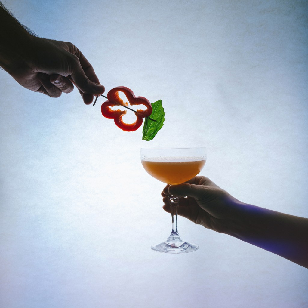 Garnish of red bell pepper and basil being held by a hand hovering over a cocktail glass with orange liquid