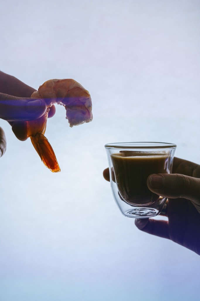 One hand holding a shrimp close to another holding a shot glass of cocktail sauce for our Image of silhouetted hand holding an orange cocktail for our menu pairing with Punch-Drunk Love post