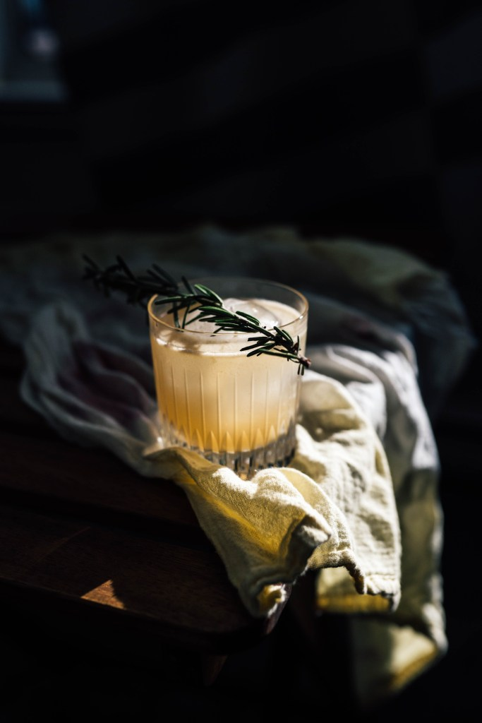 Dramatic lighting on a Ginger Buck cocktail with a rosemary sprig laying on top. The cocktail is sitting on a yellow cloth.