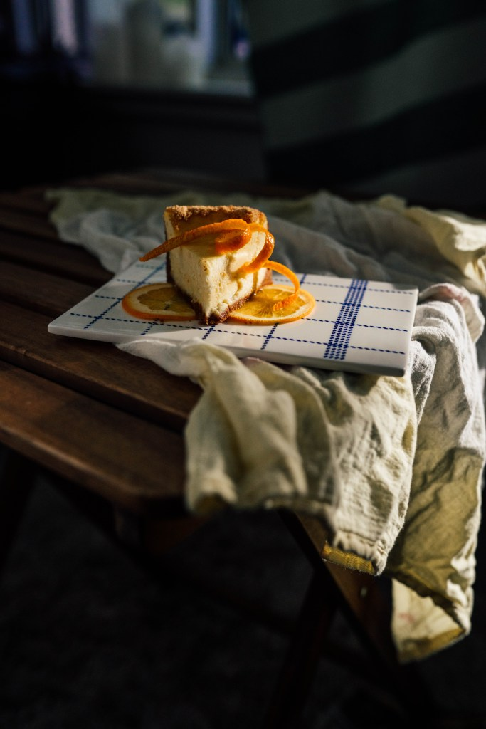 Heavily shadowed image of our citrus cheesecake that is sitting on two orange slices on a white rectangular plate with a blue grid like pattern.