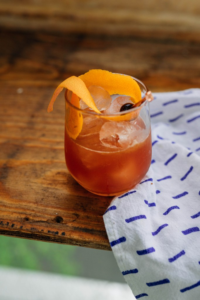 Three-quarters view of a Muddled Old Fashioned with a large orange peel garnish that wraps around the inside of the glass. There is a white napkin with blue dashes on the right hand side of the image and the majority of the image is a wet wood particle board.