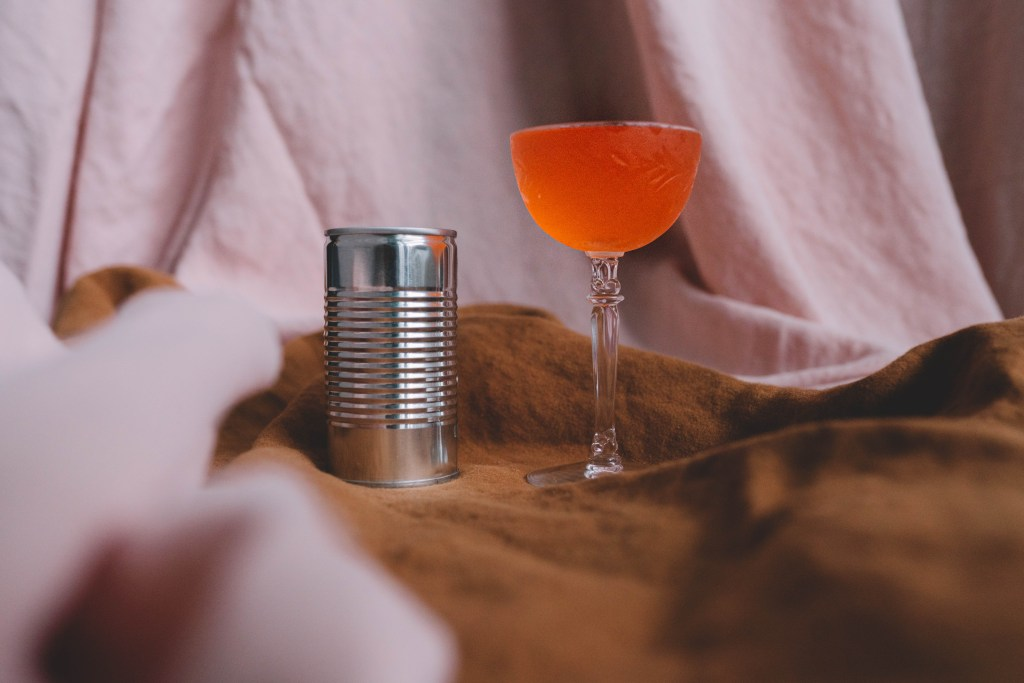 Close up of the Light and Day cocktail sitting in a Nick and Nora glass with a slight engraving seen in the glass. The color of the cocktail is a deep orange and it is set against a blush and rust colored draping. A small tin can sits next to the cocktail.