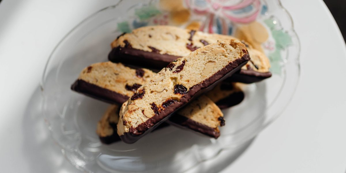 Top-down view of the chocolate-dipped cherry almond biscotti. The Biscotti is stacked and you can see the glass plate below it and the red ribbon and bells that color the glass plate.