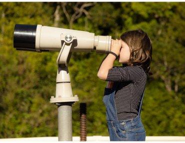 Girl looks through huge binoculars at Zealandia