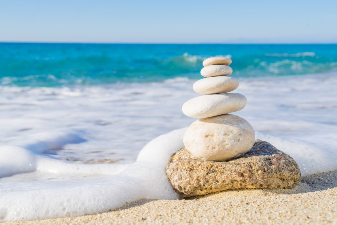 ocean with foam and stacked rocks on a beach, mindfulness