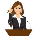 female speaker standing behind a podium with microphones. Speaker
