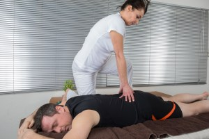 Man on massage table with female Reiki practitioner working at waist level