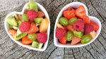 fresh fruits in two white, heart-shaped, small bowls
