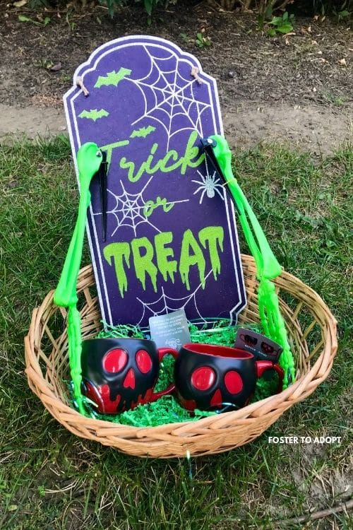 Trick or Treat sign with Skelton hands and Disney cups made into a boo basket for Halloween.