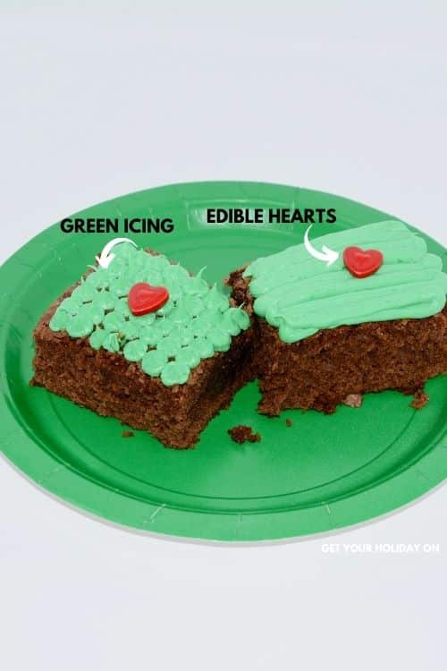 Green icing on top of the brownie and edible red hearts to complete the Grinch brownie.