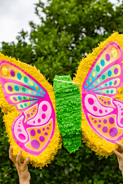 A butterfly piñata filled with the best bachelorette piñata fillers for a bachelorette party.