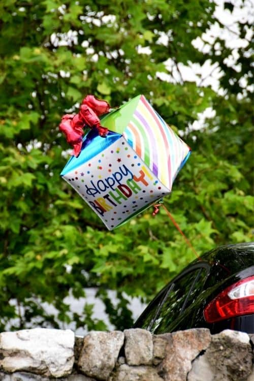 A birthday balloon hanging off of the car for a fun birthday surprise for teens.