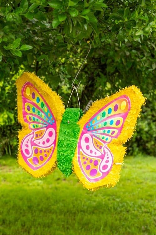 A butterfly piñata hanging in a tree that is for a bridal party.