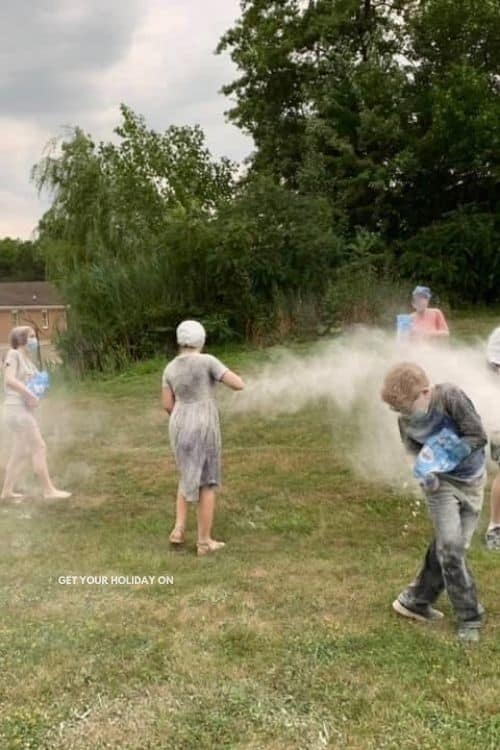 Teenagers having flour fights in the backyard of our church outside for large group bible games.