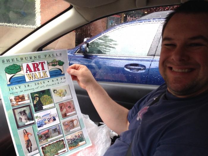 Keith Urkiel proudly holds the poster advertizement for the Shelburne Falls Art Walk taking place on July 18th Featuring Kristen Brunton of Get Your Roll On Quilling who will be quilling live at Mormor art gallery and store where you can currently buy Kristen's latest and greatest creations.