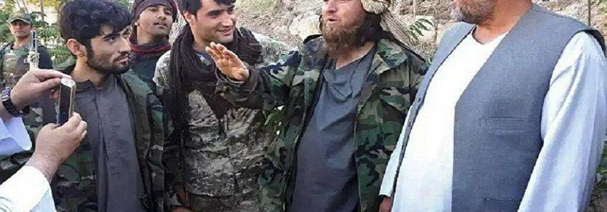 ISIS child with a gun slung over his shoulder smiles as he surrenders to authorities along with 150 terrorist in Afghanistan