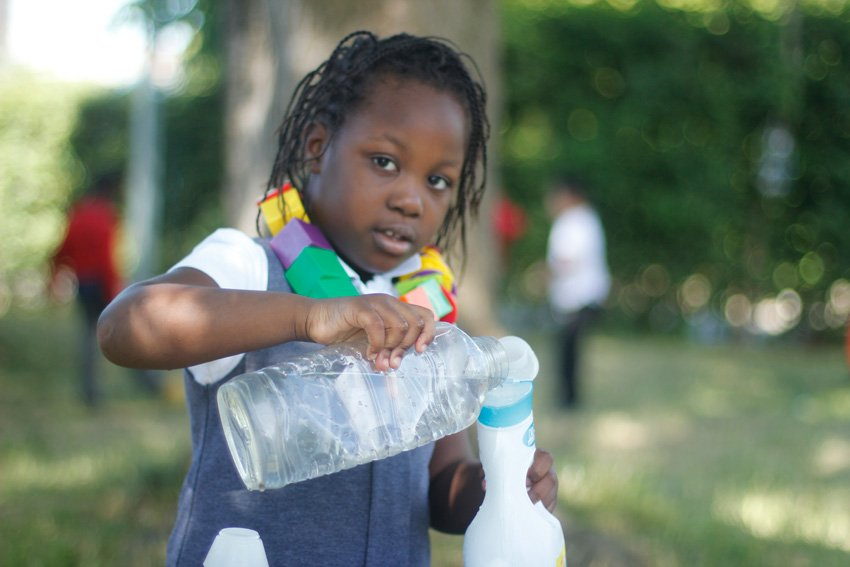 Young girl pouring water into another container
