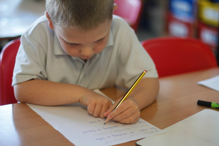 Boy concentrating on his handwriting during an English lesson