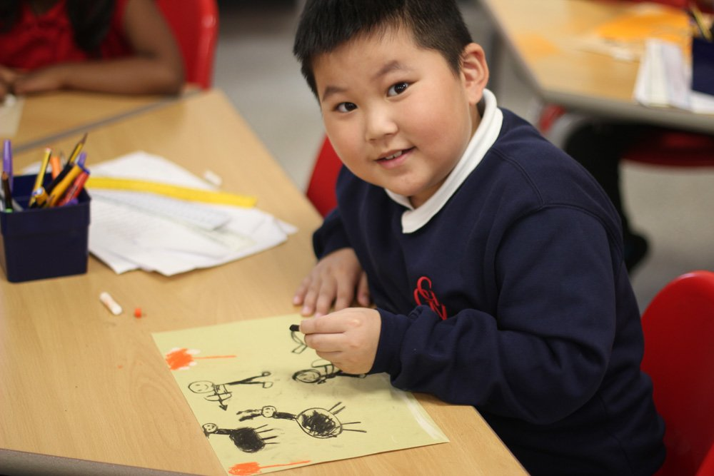 Boy drawing within an art class