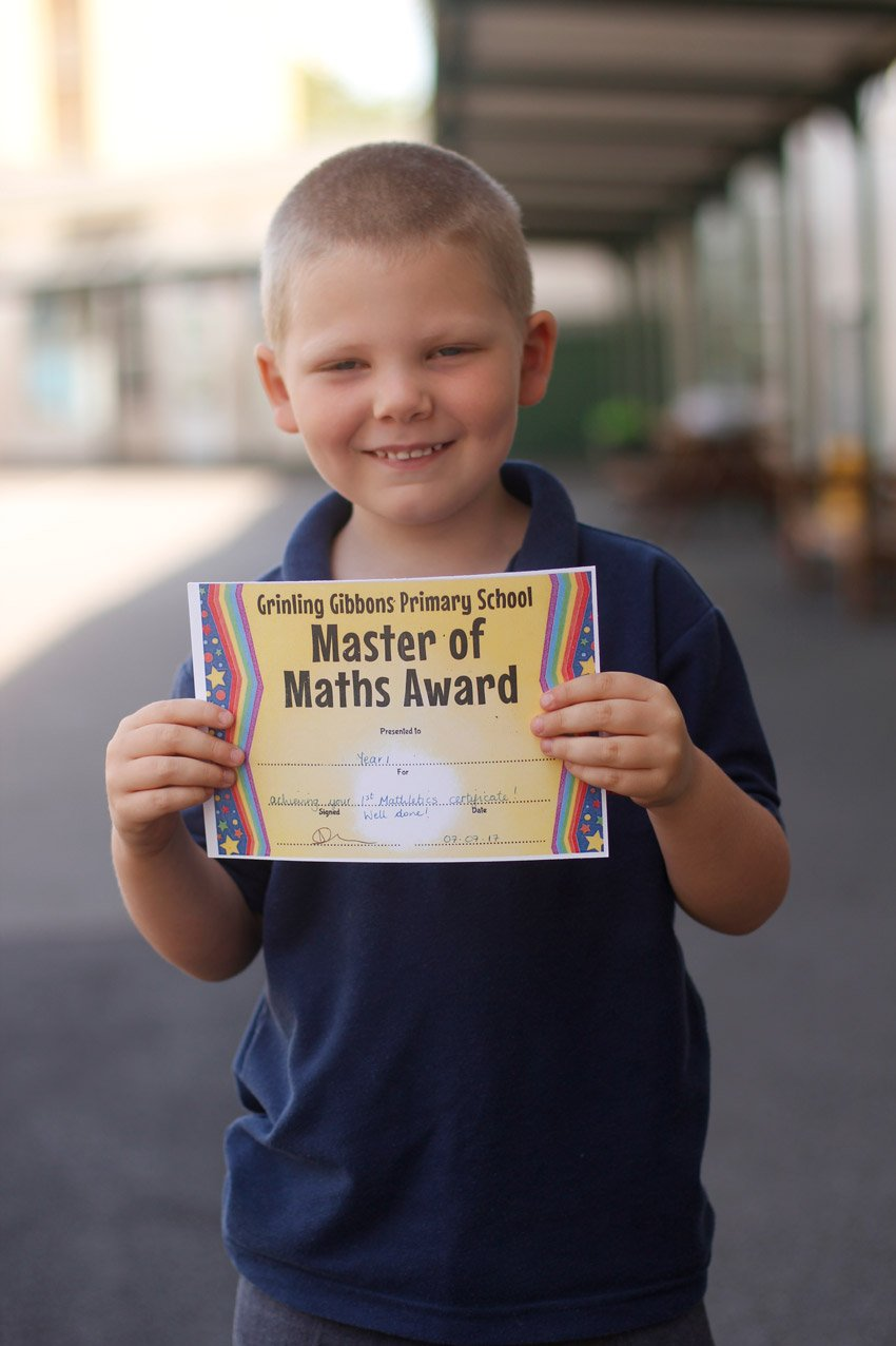 Proud boy showing off his maths award