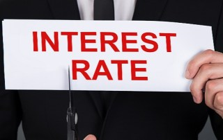man-holding-interest-rate-sign-with-scissors-cutting