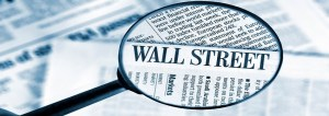 Close-up on magnifying glass against Wall Street News