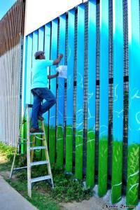 Enrique painting on the border wall in Playas de Tijuana. Photo by: Noemi Ramirez