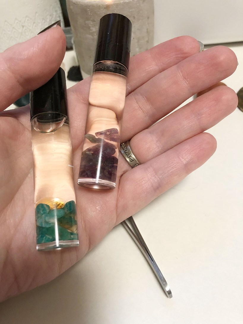 a hand holding two roller top bottles with essential oils and crystals to clear negative energy