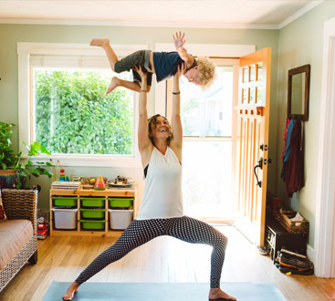 Woman in yoga pose holding child
