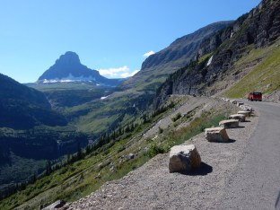 A classic tour bus heads up Logan Pass towards the visitor center in Glacier NP.