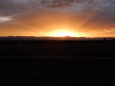 The sun finds that narrow strip of clear sky between the clouds and the mountains as I ride into Denver.