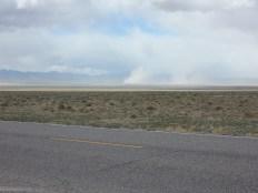 A few dust devils dance on the salt flat north of Rachel.
