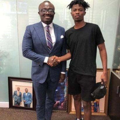 Kwesi Arthur receives a gold wrist watch from Bola Ray