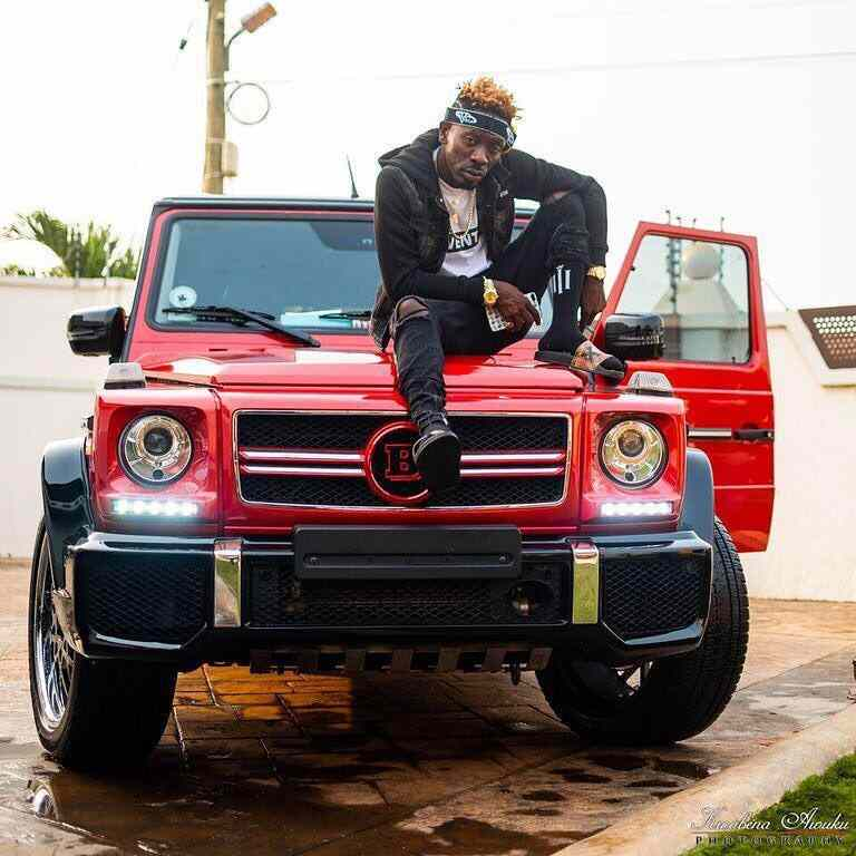 Shatta Wale posing with his latest cars